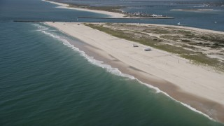 AX91_229 - 4K stock footage aerial video tilt from water, revealing RVs on a beach and Shinnecock Inlet, Southampton, New York