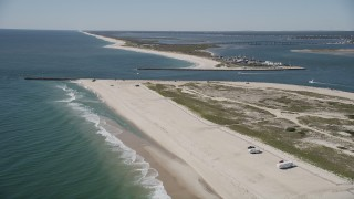 AX91_230 - 4K stock footage aerial video fly over RVs on a beach to approach Shinnecock Inlet, Southampton, New York