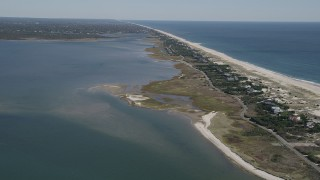 AX91_231 - 4K stock footage aerial video of flying away from beach and coastal homes by Shinnecock Bay, Southampton, New York
