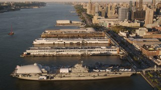 AX93_008 - 4K stock footage aerial video Approaching the USS Intrepid, tilting down, New York, New York, sunset