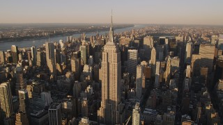 AX93_041 - 4K stock footage aerial video Flying by the Empire State Building, Midtown Manhattan, New York, sunset