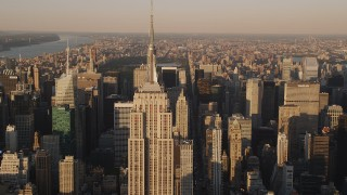 AX93_042 - 4K stock footage aerial video Flying by the Empire State Building, Midtown Manhattan, New York, sunset