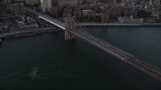 AX93_081 - 4K stock footage aerial video Panning across Brooklyn Bridge to Lower Manhattan side, New York, New York, sunset
