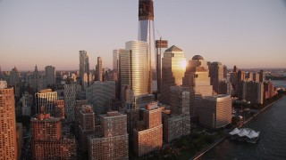 AX93_101 - 4K stock footage aerial video Flying by World Trade Center, Lower Manhattan, skyscrapers, New York, sunset