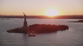 AX93_107 - 4K stock footage aerial video Flying by the Statue of Liberty, New York, New York, sunset