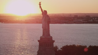 AX93_108 - 4K stock footage aerial video Flying by the Statue of Liberty, New York Harbor, New York, New York, sunset