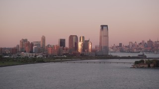 AX93_117 - 4K stock footage aerial video Flying by Goldman Sachs Tower, Downtown skyline, Jersey City, New Jersey, sunset