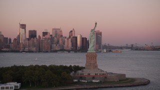 AX93_120 - 4K stock footage aerial video Flying by Statue of Liberty, Lower Manhattan skyline, New York, sunset