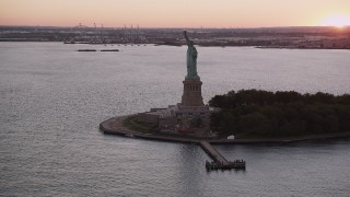 AX93_123 - 4K stock footage aerial video Flying by the Statue of Liberty, New York, New York, sunset