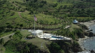 AX96_163 - 5k stock footage stock footage aerial video orbiting flag and pool and fly away on Little St James Island, St Thomas, Virgin Islands
