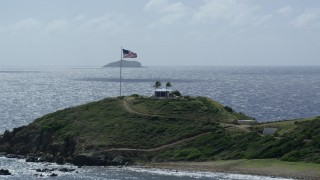 AX96_165 - 5k stock footage stock footage aerial video American flag and circular building on Little St James Island, St Thomas, Virgin Islands