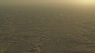 CAP_001_001 - HD stock footage aerial video of a desert road through sand dunes at sunrise in Al Gharbia, Abu Dhabi, UAE