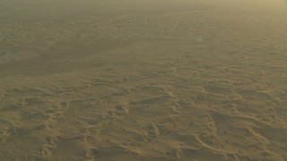 CAP_001_007 - HD stock footage aerial video of flying over hazy desert sand dunes at sunrise, Al Gharbia, Abu Dhabi, UAE