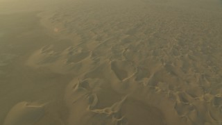 CAP_001_012 - HD stock footage aerial video of orbit and fly away from desert sand dunes at sunrise in Al Gharbia, Abu Dhabi, UAE