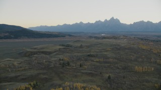 CAP_002_001 - HD stock footage aerial video fly over hills toward mountains, Jackson Hole, Wyoming, twilight