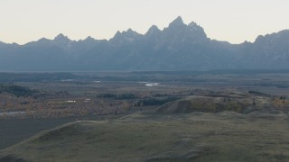 CAP_002_002 - HD stock footage aerial video fly over hills toward rugged mountains, Jackson Hole, Wyoming, twilight