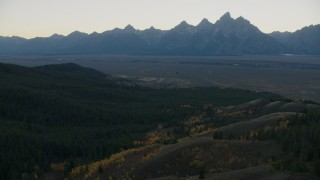 CAP_002_009 - HD stock footage aerial video of mountains seen from evergreen forest, Jackson Hole, Wyoming, twilight