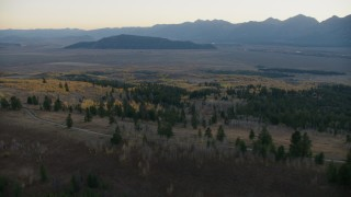 CAP_002_012 - HD stock footage aerial video fly over country road and autumn trees, Jackson Hole, Wyoming, twilight
