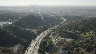 CAP_004_008 - HD stock footage aerial video of tilt from freeway in Hollywood Hills to reveal Downtown Los Angeles skyline, California