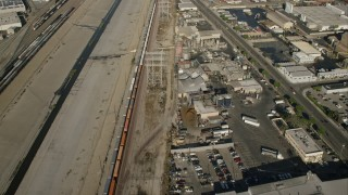 CAP_004_027 - HD stock footage aerial video reverse view of train between river and warehouses, Vernon, California