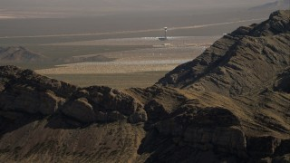 CAP_005_008 - HD stock footage aerial video flyby mountain to reveal tower at Ivanpah Solar Electric Generating System, Mojave Desert, California