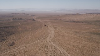 CAP_005_022 - HD stock footage aerial video of a dirt road by an arid valley, Mojave Desert, California