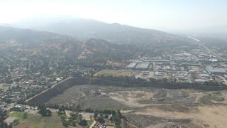 CAP_006_003 - HD stock footage aerial video of warehouse buildings and a large landfill area in Sun Valley, California