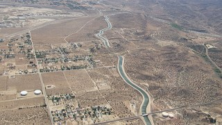 CAP_006_007 - HD stock footage aerial video pass rural homes and desert around the California Aqueduct in Palmdale, California