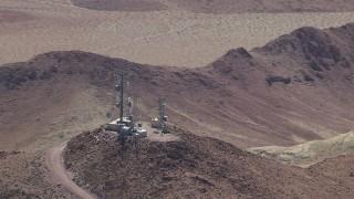 CAP_006_016 - HD stock footage aerial video of radio towers on a Mojave Desert mountain in San Bernardino County, California