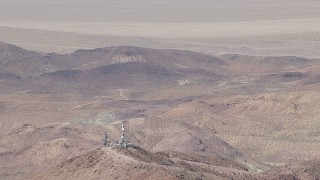CAP_006_019 - HD stock footage aerial video of a reverse view of a group of radio towers and Mojave Desert mountains in San Bernardino County, California