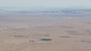 CAP_006_020 - HD stock footage aerial video approach a crop field and a Mojave Desert monastery in Newberry Springs, California