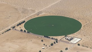 CAP_006_023 - HD stock footage aerial video of a reverse view of a crop field beside a Mojave Desert monastery in Newberry Springs, California