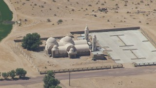 CAP_006_025 - HD stock footage aerial video of reverse view of a Mojave Desert monastery in Newberry Springs, California
