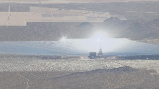CAP_006_031 - HD stock footage aerial video of glowing boiler atop a power tower at the Ivanpah Solar Electric Generating System in California