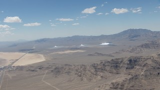 CAP_006_047 - HD stock footage aerial video of a view of the three solar arrays at Ivanpah Solar Electric Generating System in California next to a highway