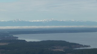 CAP_009_007 - HD stock footage aerial video of the snowy Olympic Mountain range seen from Puget Sound, Washington