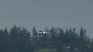 CAP_009_009 - HD stock footage aerial video track an airplane flying over Puget Sound and evergreen trees, Washington
