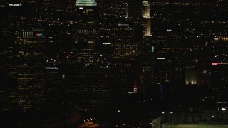 CAP_010_014 - HD stock footage aerial video tilt from Downtown Los Angeles city buildings to Figueroa and Wilshire skyscraper at night, California