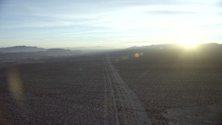 CAP_011_001 - HD stock footage aerial video of following power lines through the desert to approach Daggett, California at sunrise