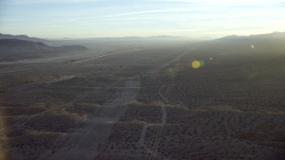 CAP_011_002 - HD stock footage aerial video follow power lines through the desert to approach I-40 in Daggett, California at sunrise