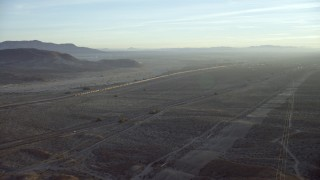 CAP_011_003 - HD stock footage aerial video approach I-40 and a train in the desert in Daggett, California at sunrise