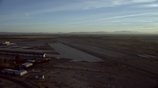 CAP_011_006 - HD stock footage aerial video approach and pan across the Barstow-Daggett Airport in California at sunrise