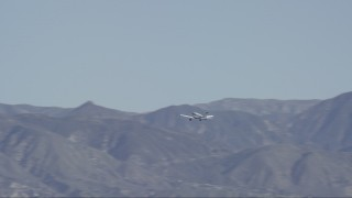 CAP_012_001 - HD stock footage aerial video of a small airplane flying by the Verdugo Mountains in Burbank, California