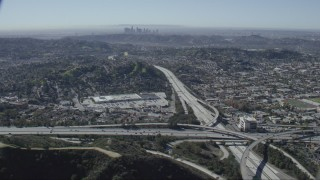 CAP_012_011 - HD stock footage aerial video of the 2 and 134 freeway interchange in Glendale, California, Downtown Los Angeles skyline in background