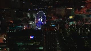 CAP_013_060 - HD stock footage aerial video of a Ferris wheel at nighttime, Downtown Atlanta, Georgia