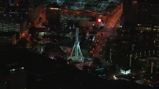 CAP_013_063 - HD stock footage aerial video of flying away from a Ferris wheel at nighttime, reveal skyscraper, Downtown Atlanta, Georgia