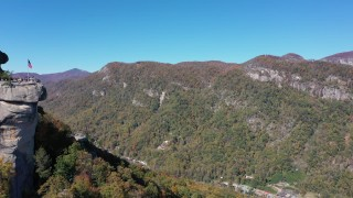 CAP_014_005 - 2.7K stock footage aerial video of flying by the rock formation to approach mountains at Chimney Rock in North Carolina