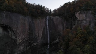 CAP_014_013 - 2.7K stock footage aerial video approach a clifftop waterfall at sunset, Chimney Rock, North Carolina
