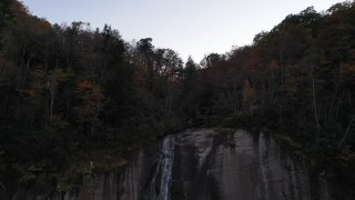 CAP_014_014 - 2.7K stock footage aerial video ascend over a clifftop waterfall at sunset, Chimney Rock, North Carolina