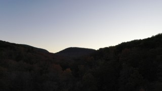 CAP_014_015 - 2.7K stock footage aerial video ascend over forest for view of distant mountains at sunset, Chimney Rock, North Carolina
